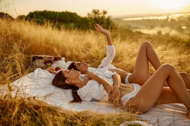 フィールドで毛布の上に横たわっているランジェリーの2人のセクシーな女性。牧草地でのレジャー、日没時のリラクゼーション、自由な気持ちでスリムな体の女性