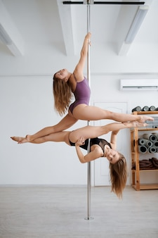 Two sexy women on pole-dancing training