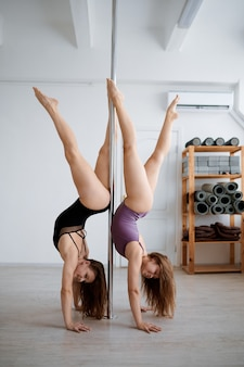Two sexy women on pole-dancing workout