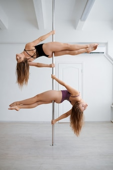 Two sexy women practice pole-dancing, training in class. professional female dancers exercising in gym, pole dance