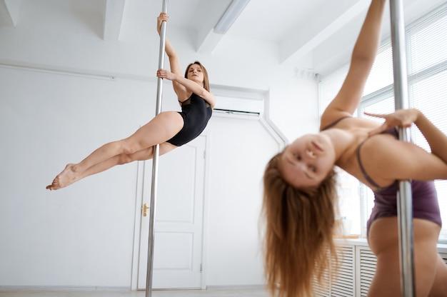 Две сексуальные женщины занимаются танцами на шесте, тренируются в классе. профессиональные танцовщицы, тренирующиеся, танец на пилоне