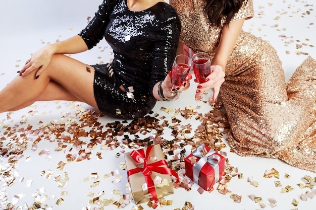 Two   sexy women in  in red christmas santa claus holiday hat sitting on floor with shining golden confetti.  wearing  sparkly  evening  dress.