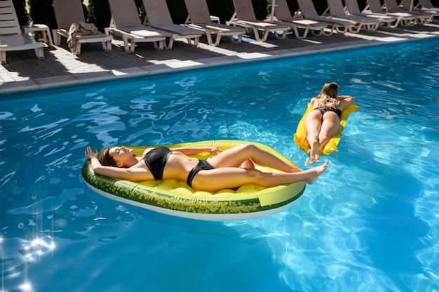 리조트 수영장에서 풍선 매트리스에 일광욕 두 섹시한 여성. 아름다운 소녀는 화창한 날, 매력적인 여성의 여름 휴가에 수영장에서 휴식을 취합니다.