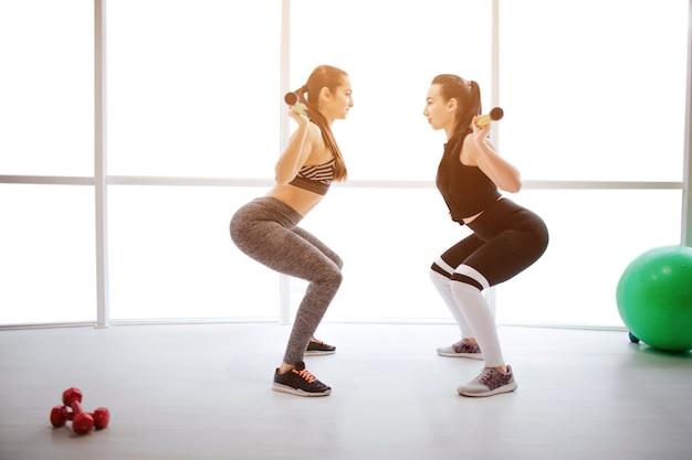 피트 니스 룸에서 운동을 하 고 두 섹시 한 젊은 여성