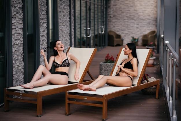 Две сексуальные молодые женщины расслабляются на шезлонге