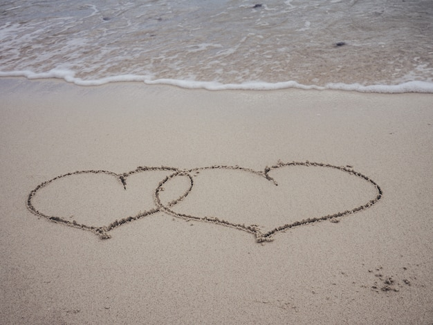 Two shape heart writing on sand beach with waves ocean