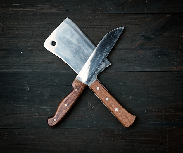 Two sharp knives lie on a brown wooden surface, kitchen items are crossed