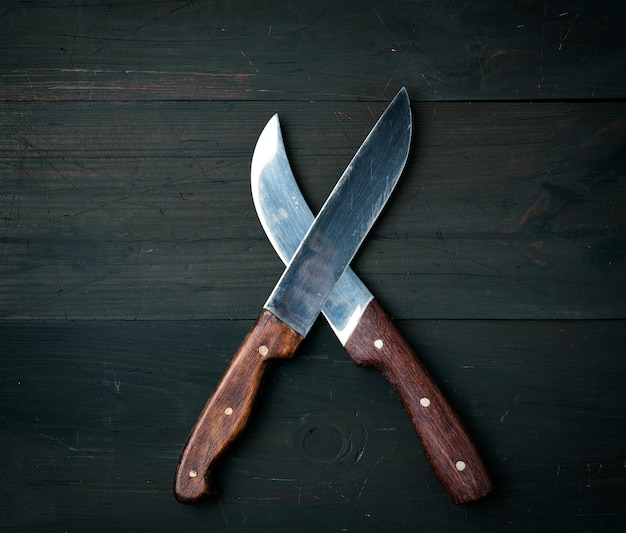 Two sharp knives lie on a brown wooden surface