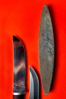 빨간색 배경에 두 개의 날카로운 칼