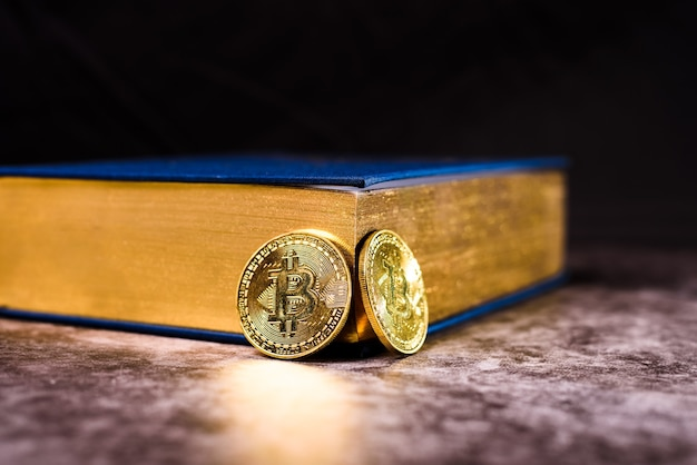 Two shiny golden bitcoin coins next to a wealth secrets book.