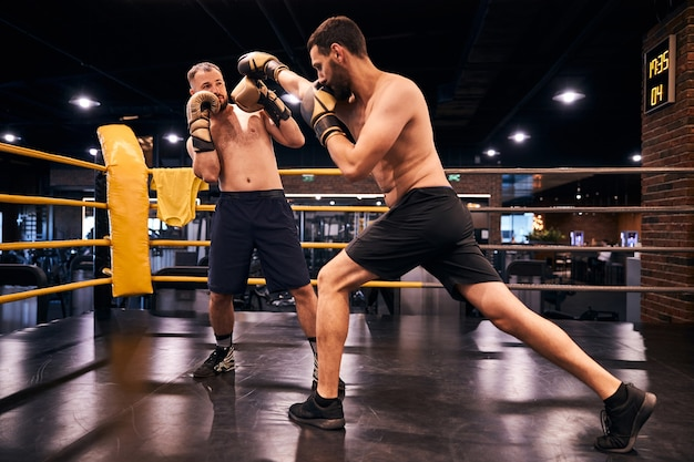 Two shirtless muscular men in boxing gloves having a sparring fight