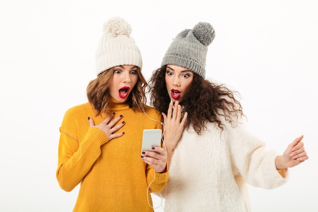 Two shocked girls in sweaters and hats standing together while using smartphone over white wall
