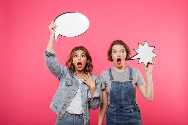 Two shocked ladies friends holding speech bubbles.