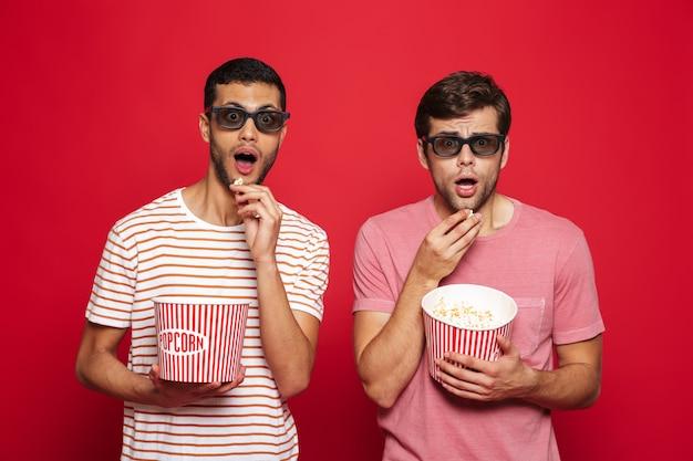 Двое потрясенных молодых людей стоят изолированно над красной стеной и едят попкорн в 3d-очках
