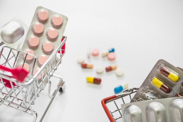 Two shopping carts filled with blister pack of medicine on white background