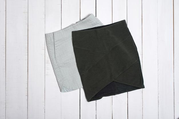 Две короткие юбки на белом фоне деревянных. концепция моды.