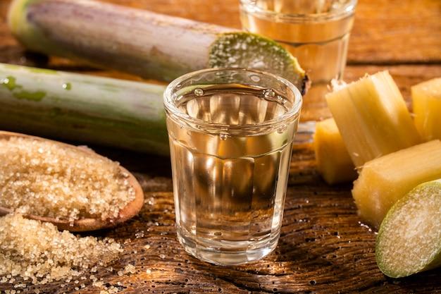 素朴な木製のスペースで分離された砂糖とサトウキビとブラジルの金カシャーサの2つのショットグラス。