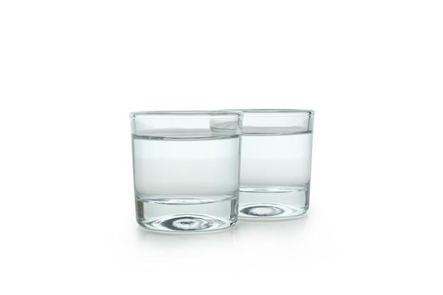 Две рюмки напитка, изолированные на белой стене