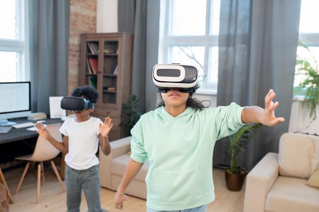 Двое братьев и сестер в гарнитурах виртуальной реальности и повседневной одежде смотрят онлайн-видео на большом виртуальном дисплее, стоя перед камерой в гостиной.