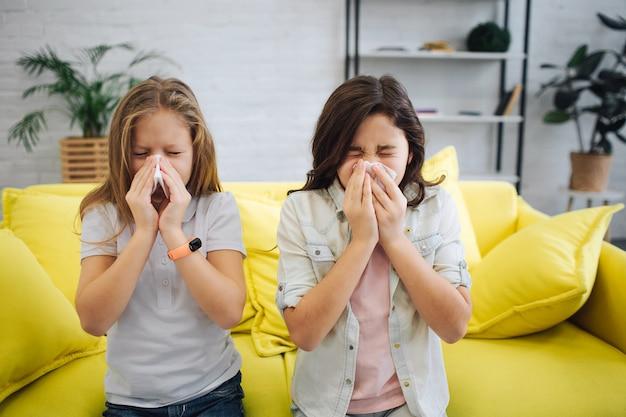 두 명의 아픈 십대들이 방에 서서 재채기를합니다. 그들은 하얀 티슈를 손에 쥐고 있습니다. gitls는 고통받습니다. 그들은 아 sick니다.