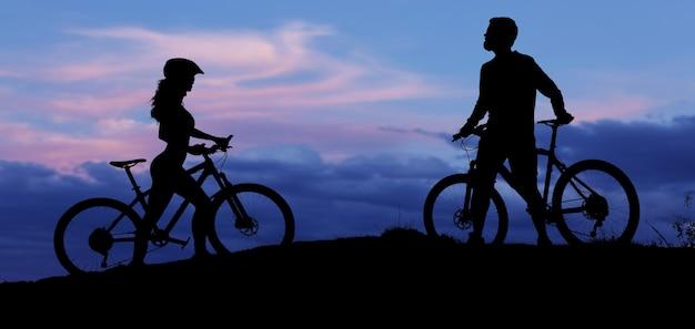 Два силуэта велосипедистов на фоне заката спортивный парень и девушка на современных горных велосипедах