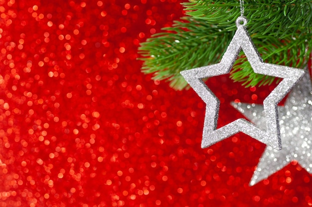 Two silver star on a christmas tree branch on a red shining background from bokeh