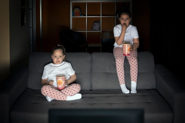 Two sister girls are watching a tv show on tv with interest on the couch in a dark room in the eveni...