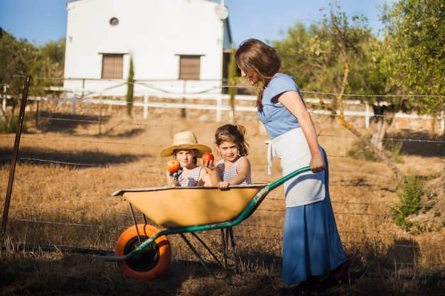 Two sister holding red apple sitting in wheelbarrow being pushed by woman