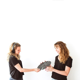 Two sister holding vinyl record isolated over white backdrop