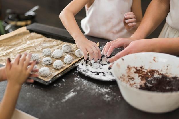 2人の姉妹と母親の台所でチョコレートクッキーを準備します。