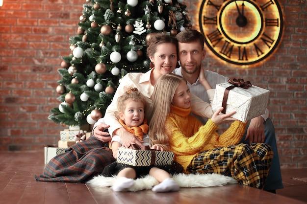 두 자매와 그들의 부모는 크리스마스 트리 근처에 앉아
