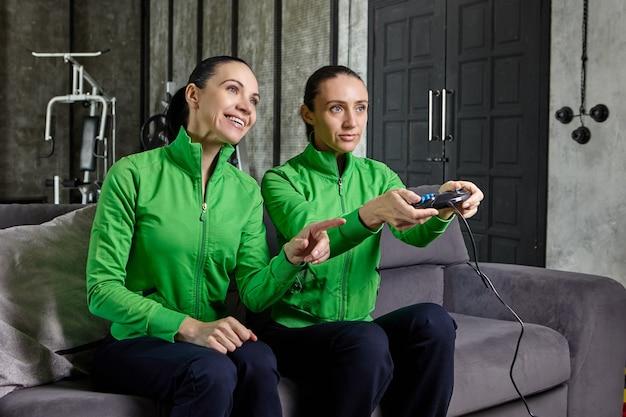 Две сестры играют в киберспортивные видеоигры с помощью консоли