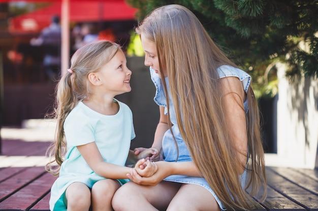 二人の姉妹が公園のベランダに一緒に座っています