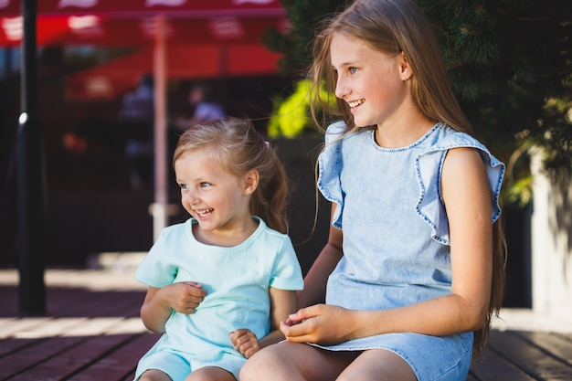 Two sisters are sitting together on the veranda in the park