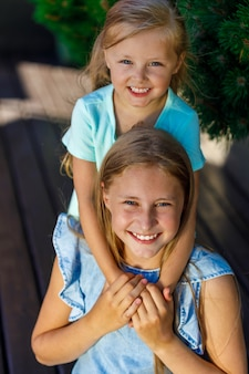 Two sisters are sitting on the veranda in nature