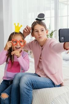 自宅で自撮りをしている2人の姉妹