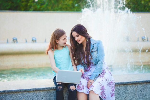 Two sisters, beautiful brunette girl and young girl walking in the city, sitting by the fountain and talking, looking at the laptop