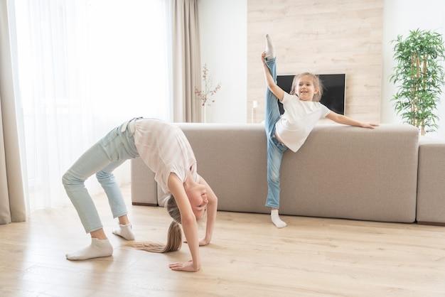 Две сестры делают упражнения на растяжку йоги в гостиной дома