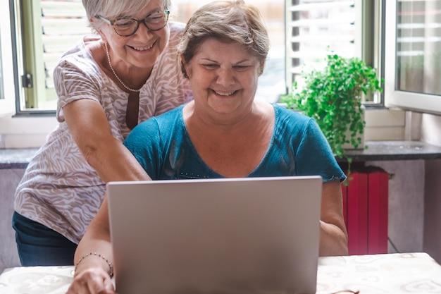 Two sisters or friends having fun using together the same laptop computer. following social media and laughing, inside home