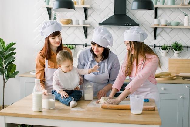 2人の姉妹、祖母と小さな赤ちゃんの娘が母の日にキッチンでホリデーパイを料理、実生活のインテリアでカジュアルなライフスタイルの写真シリーズ