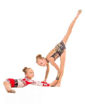 Two sisters gymnasts are working together.