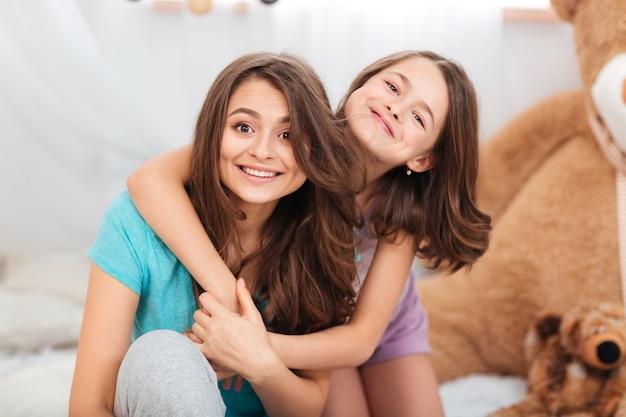 Две сестры веселятся вместе в детской комнате