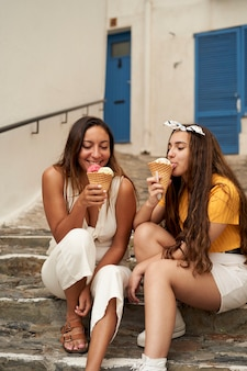 Две сестры вместе едят мороженое на открытом воздухе.