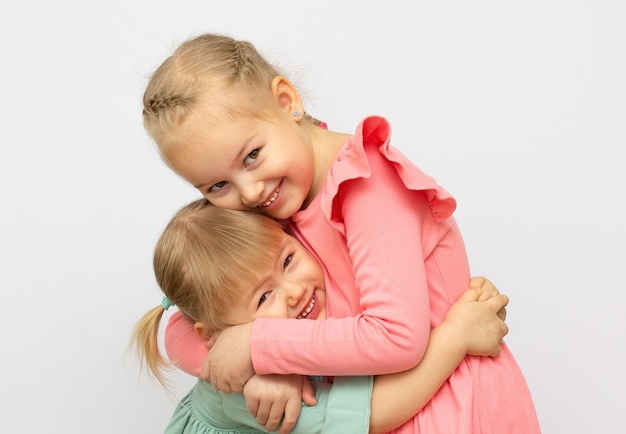 Two sisters hug each other , studio shot