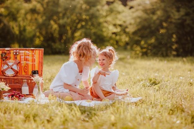 芝生の上に座ってピクニックをしている白い夏服を着た2人の姉妹。夏時間。コピースペース。