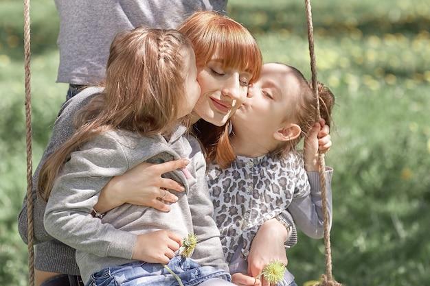 Две сестры целуют свою мать на прогулке. хорошее время