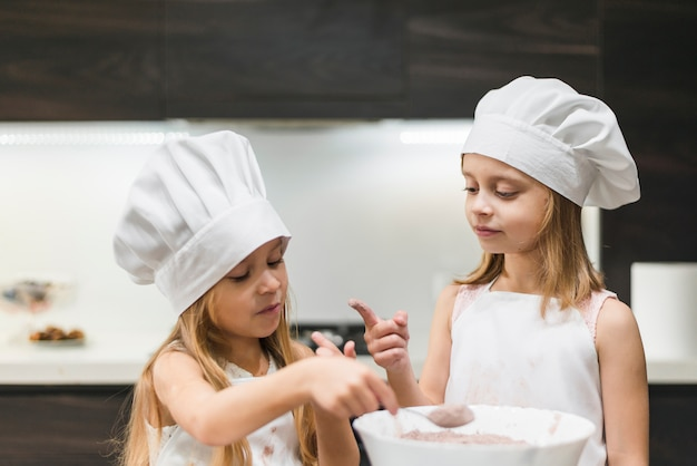 Two sisters in kitchen wearing chef's hat looking at messy finger while taking cocoa powder