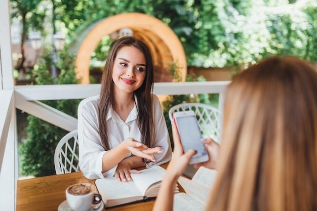 カフェで学んで話している2人の姉妹。