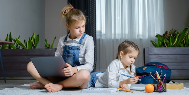Two sisters lying on the floor at living room using laptop, playing and drawing