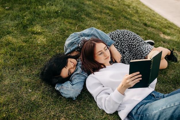 公園の緑の芝生に寝転がって本を読む二人の姉妹